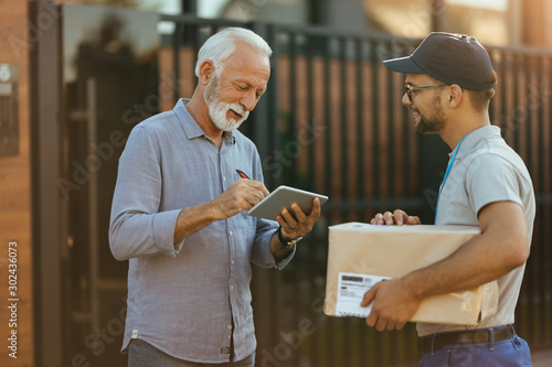 Happy mature man signing on digital tablet for a home delivery. Fototapete