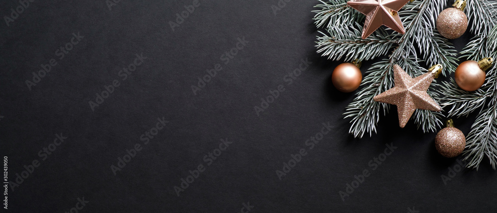 Fototapety, obrazy: Christmas banner. Black Xmas background with pine tree branch decorated cooper color balls and stars. Christmas frame, greeting card template, web banner mockup. Flat lay, top view, copy space