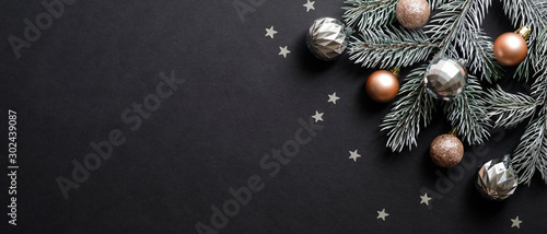 Obraz Christmas banner. Christmas tree branch decorated cooper and silver color balls on black background with confetti. Wide Xmas banner mockup, header, flyer - fototapety do salonu