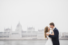Beautiful Gorgeous Bride Posing To Groom And Having Fun, Near Budapest Parliament, Space For Text, Wedding Couple