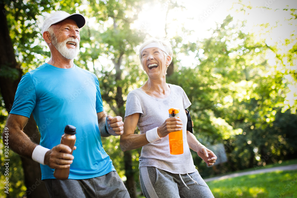 Fototapety, obrazy: Active mature couple running in the park for helathy life
