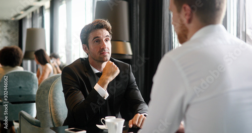 Stampa su Tela  Image of young businessman with cup of coffee communicating with colleague