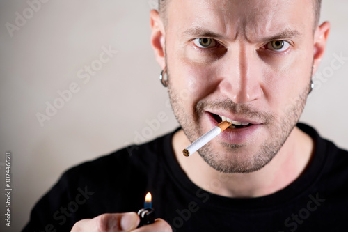 brutal man with a stern face is about to light a cigarette, close up Canvas-taulu