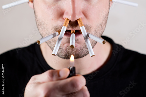 Fényképezés  the lower half of the unshaven face of a man and a lot of cigarettes in his mout