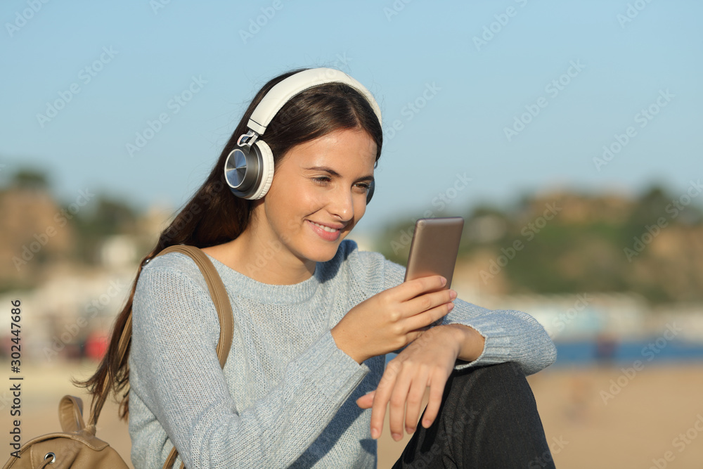 Fototapeta Happy girl listens to music with headphones and mobile phone