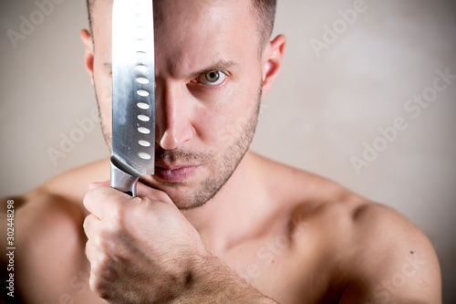 muscular man with a stern look covers his face with a kitchen knife Slika na platnu