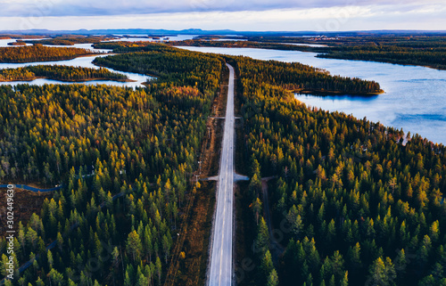 Obraz Aerial view of road through autumn forest with blue lakes in Finland. - fototapety do salonu