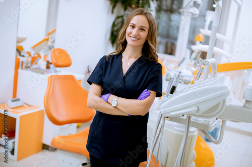 Attractive female dentist doctor standing in her office, looking at the camera