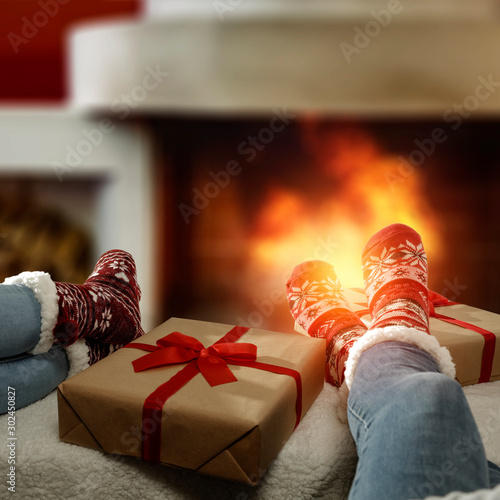 Woman legs with christmas woolen socks and home interior with fireplace.Free space for your decoration and xmas december cold night.
