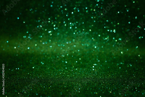 Fototapeta Green abstract glittering background. Defocused lights. Christmas greeting card. Christmas or New Year celebration concept. Copy space. Soft focus obraz