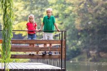 Two Children Boy And Girl Standing On Wooden Deck On A Lake Shore.