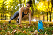 blue bottle of water on green grass. sporty woman doing outdoor workout in park on background. focus on bottle