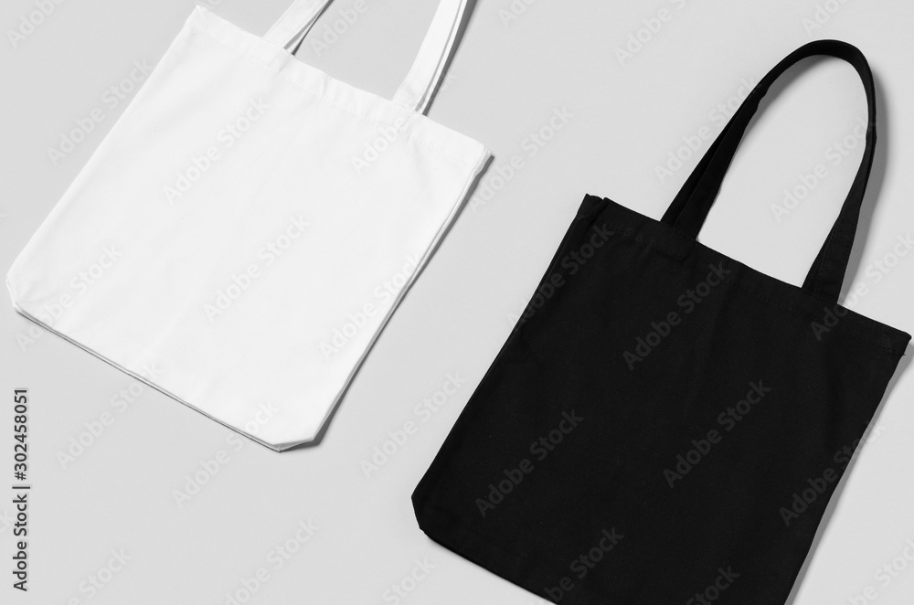 Fototapeta White and black tote bags mockup on a grey background.