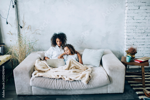 Obraz Beautiful woman with daughter watching laptop on couch - fototapety do salonu