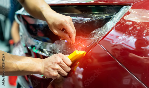 Worker install car paint protection film with spatula Canvas Print