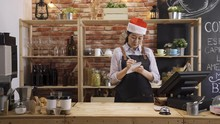 Young Asian Japanese Woman Bartender Thoughtfully Wiping Counter At Workplace In Cafe Restaurant. Barista In Apron And Christmas Santa Hatcleaning Table At Coffeehouse. Waitress Celebrate Xmas.