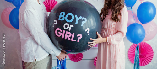 Fotografía  man and woman holding black balloon with boy or girl? on gender reveal party