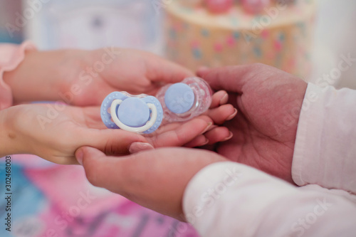 Obraz na plátně  Blue pacifier in the hands. Family waiting for little boy