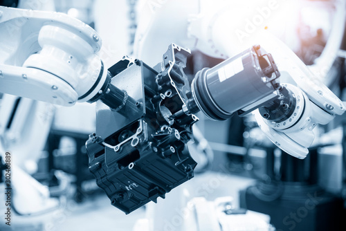 Fototapeta The automotive parts finishing process by milling spindle attach at the robotic arm. The aluminium casting gearbox parts machining process by automatic  robotic system attach the milling spindle . obraz