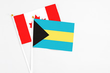 Bahamas And Canada Stick Flags On White Background. High Quality Fabric, Miniature National Flag. Peaceful Global Concept.White Floor For Copy Space.