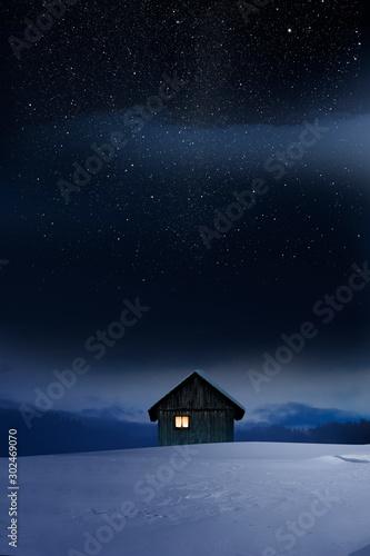 Blockhaus mit Leuchtendem Fenster im Winter bei Dämmerung - 302469070