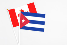 Cuba And Canada Stick Flags On White Background. High Quality Fabric, Miniature National Flag. Peaceful Global Concept.White Floor For Copy Space.