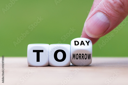 Photo Hand turns a dice and changes the word tomorrow to today, or vice versa