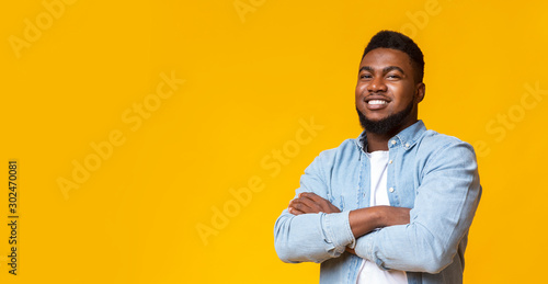 Attractive black guy with folded arms over yellow background Canvas Print