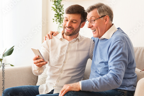 Son Teaching Senior Father Use Phone Sitting On Sofa Indoor Tapéta, Fotótapéta