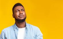 Portrait Of Suspicious Black Guy Looking Upwards At Copy Space