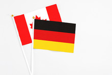 Germany And Canada Stick Flags On White Background. High Quality Fabric, Miniature National Flag. Peaceful Global Concept.White Floor For Copy Space.