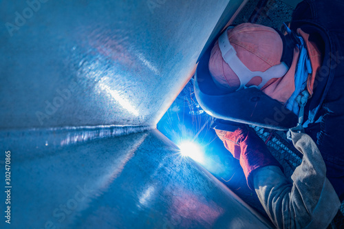 Industrial welder welding fabricated metal structure assembly on site, Welding process by Shielded Metal Arc Welding (SMAW) or Stick Welding Canvas Print