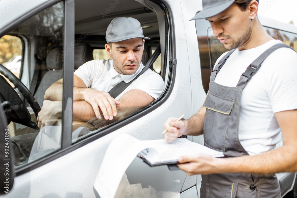 Fototapeta Delivery company employees in uniform delivering goods by cargo van vehicle, mover with a car driver checking delivery list