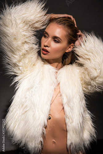 sexy naked girl with wet blonde hair in white faux fur coat looking away isolated on black - 302472262