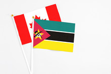 Mozambique And Canada Stick Flags On White Background. High Quality Fabric, Miniature National Flag. Peaceful Global Concept.White Floor For Copy Space.