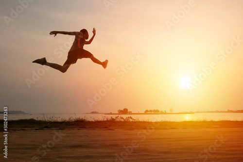 Athlete runner on road with sunset or sunrise , sport and healthy concept