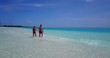 Happy couple walking across shallow sea water over white sandy stripe enjoying their vacations in Hawaii