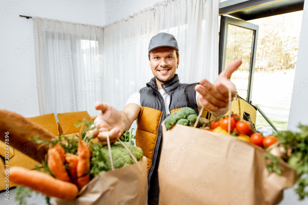 Fototapeta Portrait of a cheerful courier in uniform delivering fresh groceries home, holding paper bags full of food in front of the camera indoors