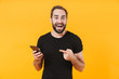 Image of surprised man wearing t-shirt smiling and holding smartphone