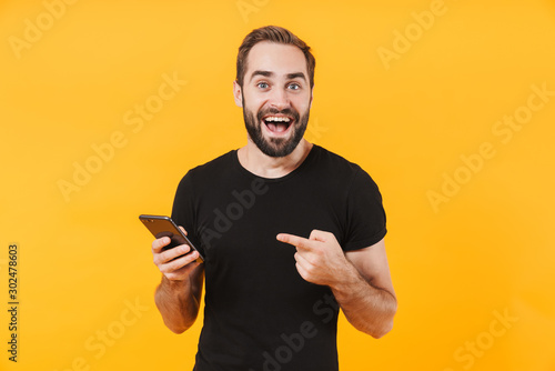 Obraz Image of surprised man wearing t-shirt smiling and holding smartphone - fototapety do salonu