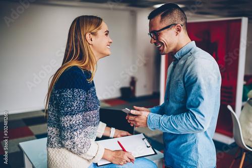 Young male and female colleagues joking during work break enjoying corporate fri Wallpaper Mural