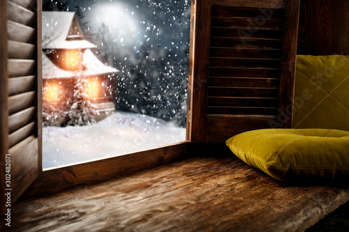 Wooden retro window sill background of free space for your decoration and pillos. Empty place for your decoration and christmas time.December night with moon on sky and winter forest with mountains.