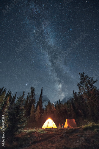 Camping in pine forest with milky way and shooting star at Assiniboine provincia Fototapeta
