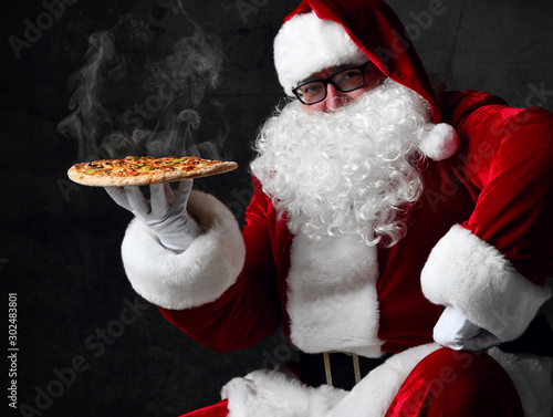 Fototapeta Happy Santa Claus is seating holding big hot steaming pizza offering, serving, brought us. New year and Xmas fast food obraz