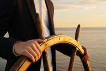 Businessman Holding Ship Rudder And Navigates In Sunset Light.
