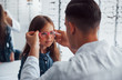 Young pediatrician in white coat helps to get new glasses for little girl