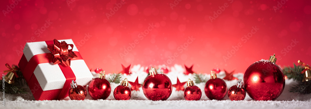Fototapeta Panoramic image of gift box and red christmas balls on snow