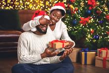 Black Girl Closing Eyes To Boyfriend While Giving Him Present