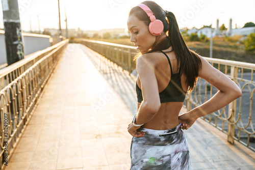 Obraz Image of seductive young woman using headphones while running - fototapety do salonu