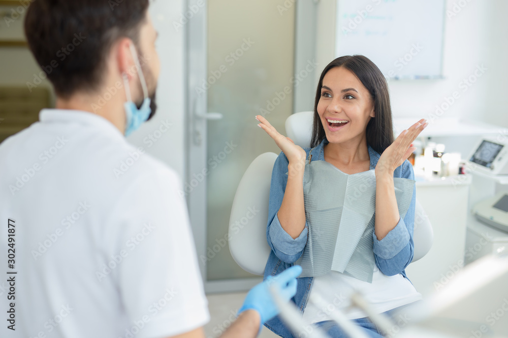 Fototapety, obrazy: woman gesturing near dentist talking to her in clinic